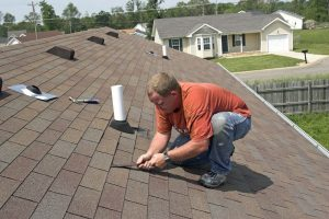 Roofing contractor repairing shingled roof