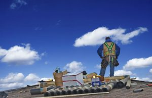 Construction Roofer Carpenter Worker on a Roof Preparing to Work.
