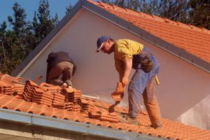 two roofers repairing a roof