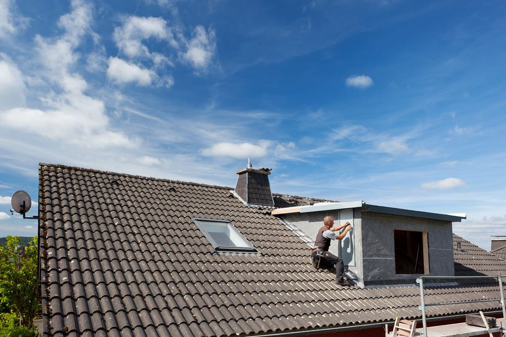 View of a rooftop with a working roofer assembling pieces to the dormer wall
