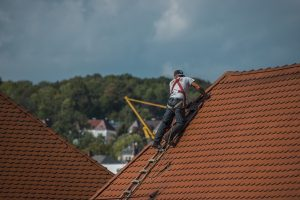 a roofer repairing a damaged roof