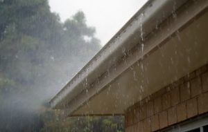 rain spilling over clogged gutters on new roof
