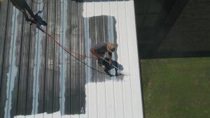 Metal roof being coated by professional roofing expert