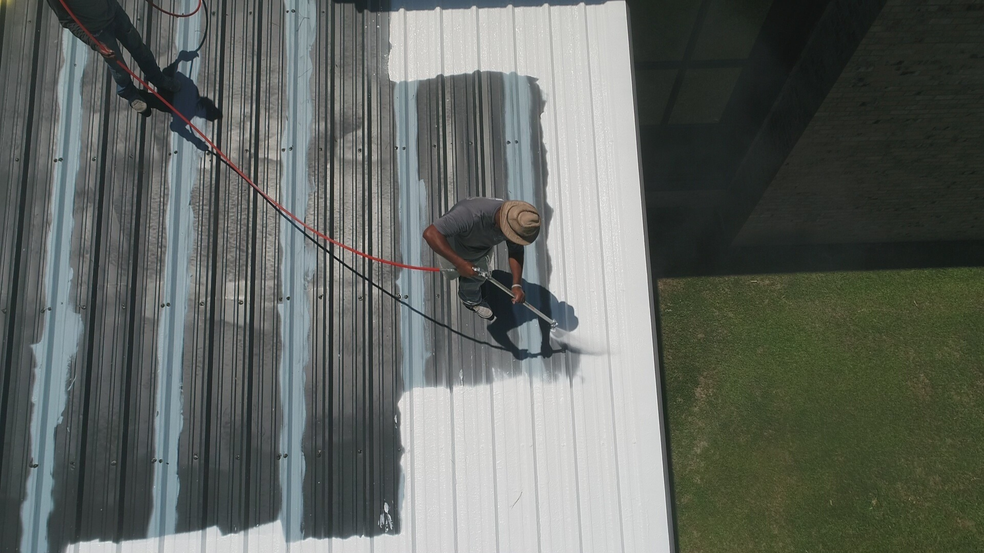 roofer applying roof coating