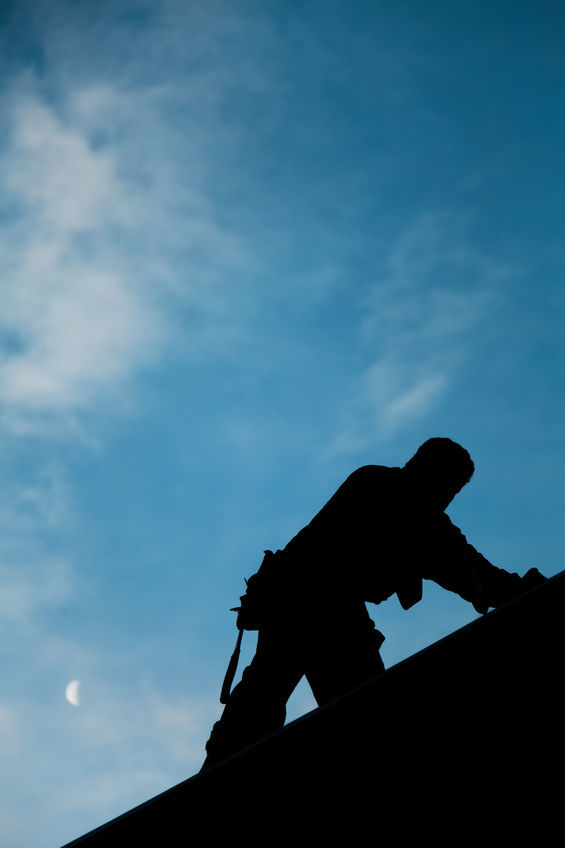 Contractor In Silhouette Working On A Roof Top Roofing